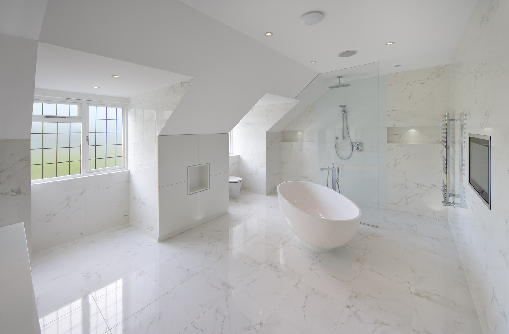 a large luxury white marble lined bathroom in an expensive home with a large oval bath. In the background is the show area behind a glass screen. A hint of green, adding a bit of colour to the scene, is visible through the frosted glass windows overlooking a garden. A large TV screen has been installed flush in the wall to the right. The square feature to the left of the bath are cupboards with a recess for decorative items in the centre. more lit recesses can be seen in the shower area.